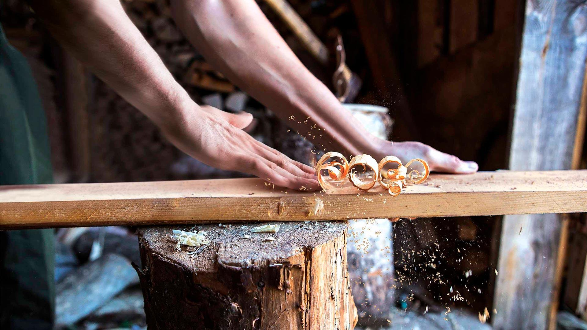 Kampagnenmotiv Hand bearbeitet ein Stück Holz wie ein Hobel