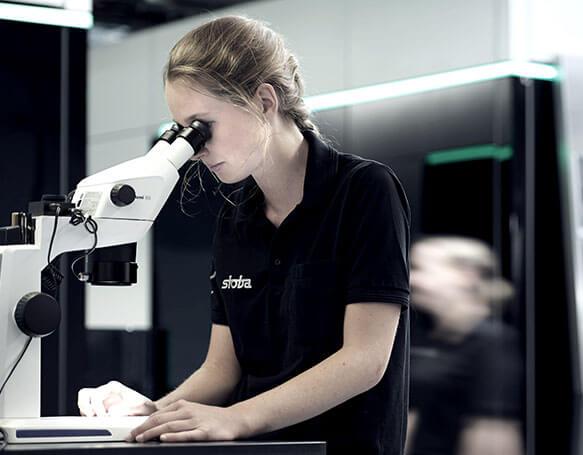 Auszubildende schaut durch ein Mikroskop