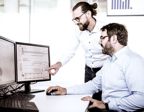 Zwei Mitarbeiter in der IT schauen auf einen Bildschirm