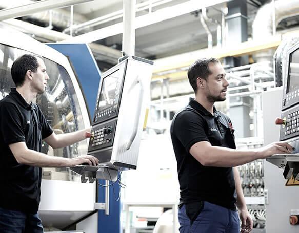 Zwei Mitarbeiter bedienen zwei Maschinen