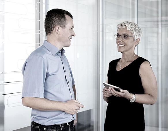 Eine Mitarbeiterin und ein Mitarbeiter führen ein Gespräch im Büro