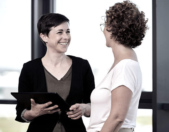 Zwei Mitarbeiterinnen führen ein Gespräch im Büro