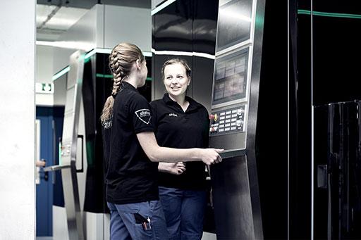 Zwei Auszubildende bedienen eine Maschine