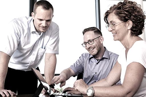 Team im Büro schaut auf einen Laptop
